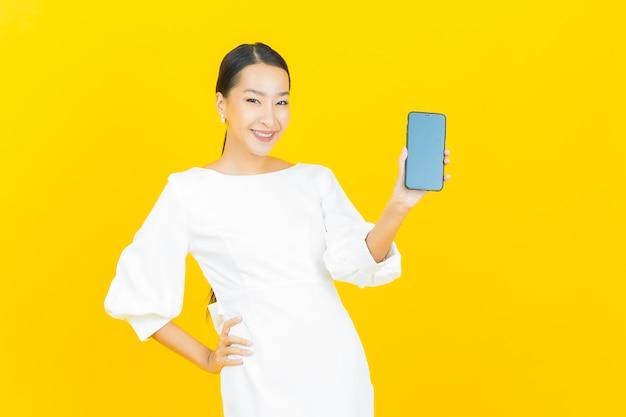 Retrato de uma bela jovem asiática sorrindo com um celular inteligente em amarelo