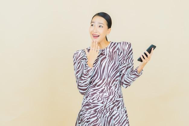 Retrato de uma bela jovem asiática sorrindo com um celular inteligente em bege.