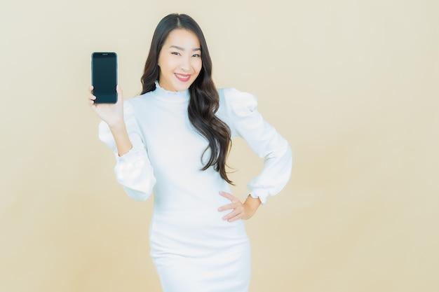 Retrato de uma bela jovem asiática sorrindo com um celular inteligente na parede colorida