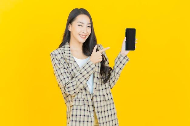 Retrato de uma bela jovem asiática sorrindo com um celular inteligente