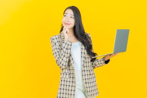 Retrato de uma bela jovem asiática sorrindo com um computador laptop