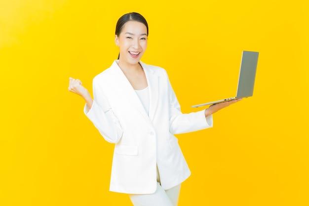 Retrato de uma bela jovem asiática sorrindo com um laptop na parede isolada