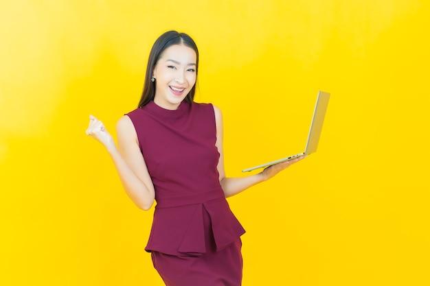 Retrato de uma bela jovem asiática sorrindo com um laptop no fundo isolado.