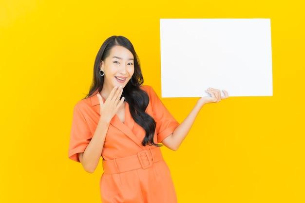 Retrato de uma bela jovem asiática sorrindo com um outdoor branco vazio em amarelo