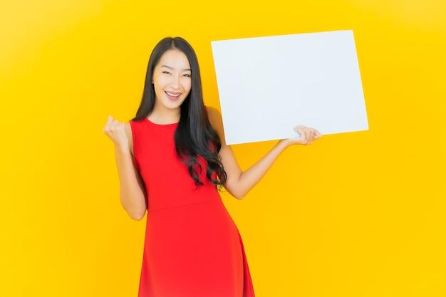 Retrato de uma bela jovem asiática sorrindo com um outdoor branco vazio na parede amarela
