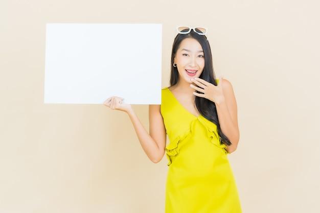 Retrato de uma bela jovem asiática sorrindo com um quadro branco vazio na parede amarela