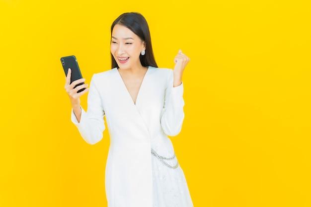 Retrato de uma bela jovem asiática sorrindo com um telefone celular inteligente