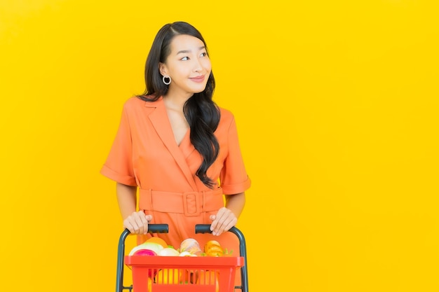 Retrato de uma bela jovem asiática sorrindo com uma cesta de supermercado em amarelo