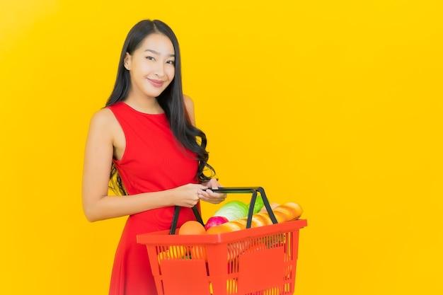 Retrato de uma bela jovem asiática sorrindo com uma cesta de supermercado na parede amarela