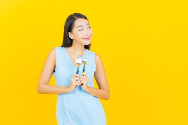 Retrato de uma bela jovem asiática sorrindo com uma colher e um garfo na parede de cor amarela