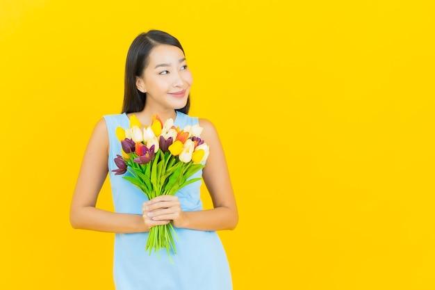 Retrato de uma bela jovem asiática sorrindo com uma flor na parede de cor amarela