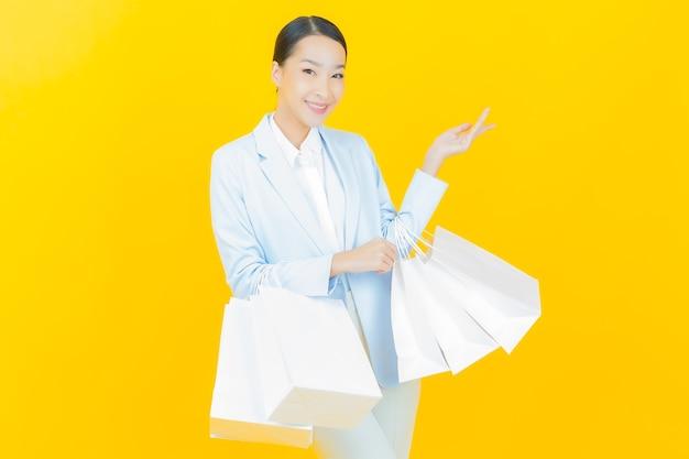 Retrato de uma bela jovem asiática sorrindo com uma sacola de compras em amarelo.