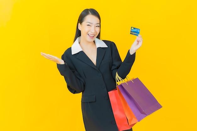 Retrato de uma bela jovem asiática sorrindo com uma sacola de compras na parede colorida