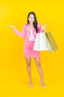 Retrato de uma bela jovem asiática sorrindo com uma sacola de compras na parede de cor amarela.