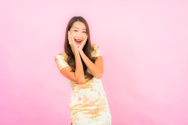 Retrato de uma bela jovem asiática sorrindo em ação com o conceito de ano novo chinês na parede cor de rosa