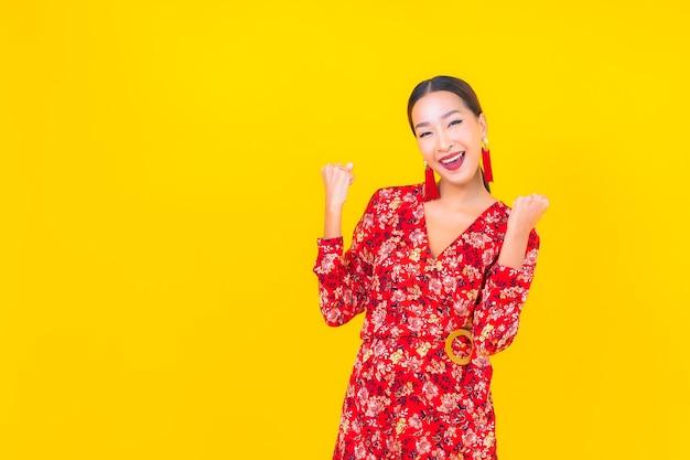 Retrato de uma bela jovem asiática sorrindo em ação no conceito de ano novo chinês na parede colorida