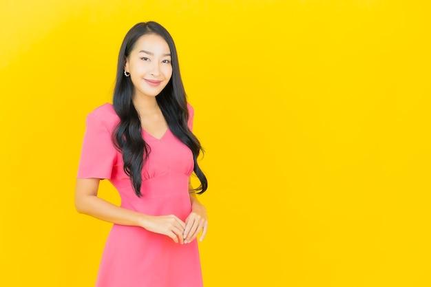 Retrato de uma bela jovem asiática sorrindo em um vestido rosa na parede amarela Foto gratuita