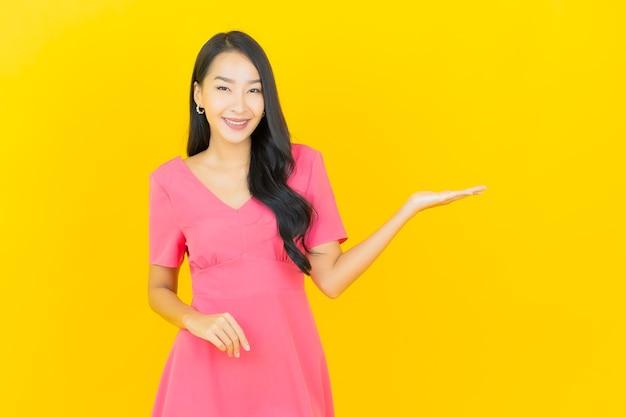 Retrato de uma bela jovem asiática sorrindo em um vestido rosa na parede amarela