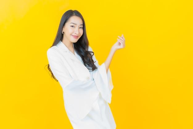 Retrato de uma bela jovem asiática sorrindo na parede amarela
