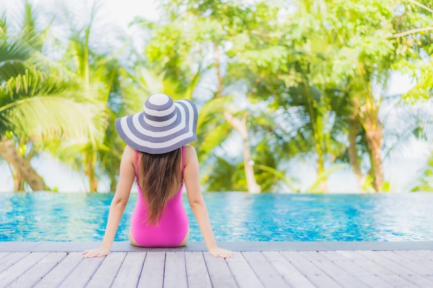 Retrato de uma bela jovem asiática sorrindo relaxando ao redor da piscina em um hotel resort em uma viagem de férias de férias