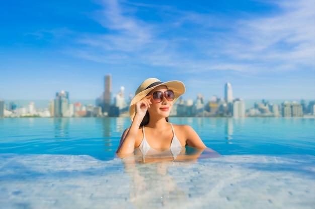 Retrato de uma bela jovem asiática sorrir relaxar o lazer ao redor da piscina ao ar livre com vista para a cidade