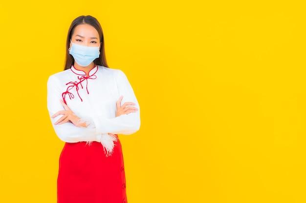 Retrato de uma bela jovem asiática usa máscara e usa álcool gel para proteger covid19 em amarelo Foto gratuita
