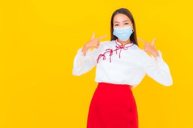 Retrato de uma bela jovem asiática usa máscara e usa álcool gel para proteger covid19 em amarelo