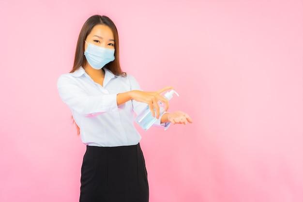 Retrato de uma bela jovem asiática usa máscara para proteção contra covid19 e coronavírus na parede rosa