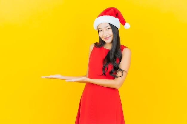 Retrato de uma bela jovem asiática usando chapéu de papai noel ou faixa para cabelo na parede amarela