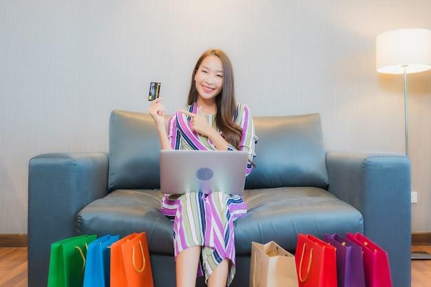 Retrato de uma bela jovem asiática usando computador, laptop ou telefone celular inteligente com cartão de crédito para fazer compras online