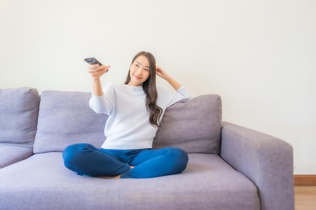 Retrato de uma bela jovem asiática usando controle remoto para mudar de canal na televisão