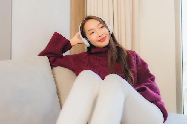 Retrato de uma bela jovem asiática usando fone de ouvido para ouvir música no sofá no interior da sala de estar