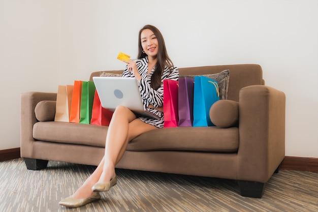 Retrato de uma bela jovem asiática usando laptop, celular inteligente ou dinheiro para fazer compras online no sofá no interior da sala de estar