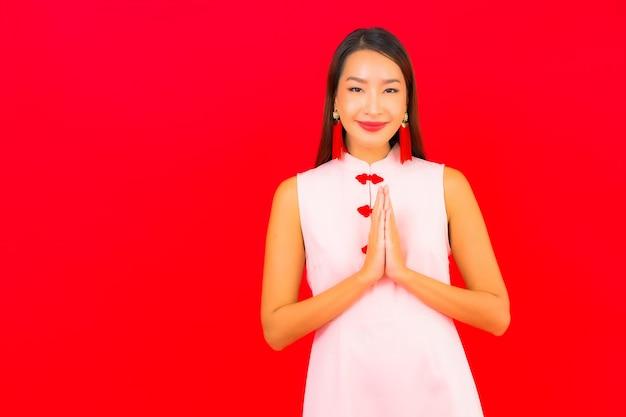 Retrato de uma bela jovem asiática usando roupas de ano novo chinês na parede vermelha