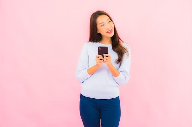 Retrato de uma bela jovem asiática usando telefone celular inteligente na parede isolada de cor rosa