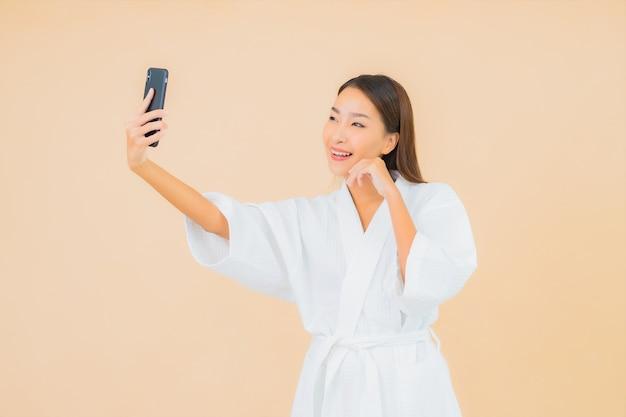 Retrato de uma bela jovem asiática usando um celular inteligente em bege