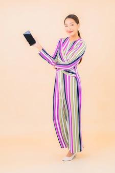Retrato de uma bela jovem asiática usando um celular inteligente na cor