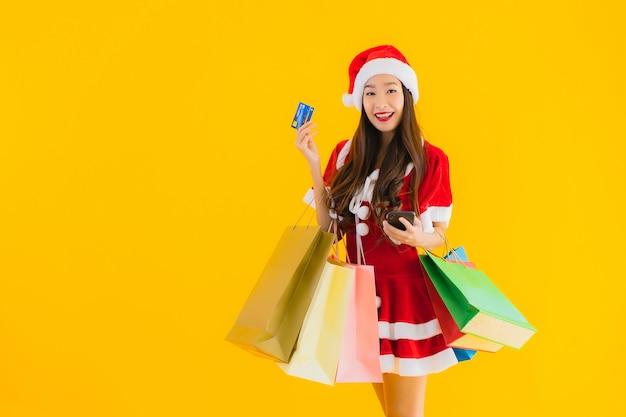 Retrato de uma bela jovem asiática usando um chapéu com roupas de natal e uma grande sacola de compras