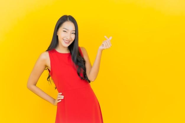 Retrato de uma bela jovem asiática usando um vestido vermelho e sorrindo com ação na parede amarela