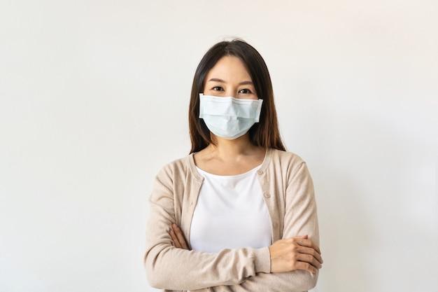 Retrato de uma bela jovem asiática usando uma máscara cirúrgica durante a crise da pandemia de coronavírus em fundo branco. novo estilo de vida normal, conceito de cuidados de saúde. copie o espaço
