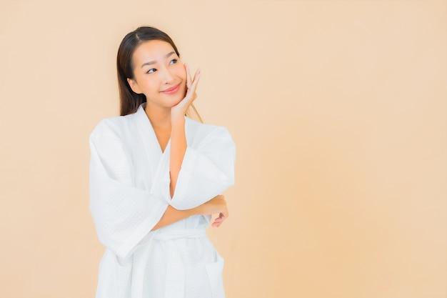 Retrato de uma bela jovem asiática vestindo um roupão de banho com um sorriso em bege