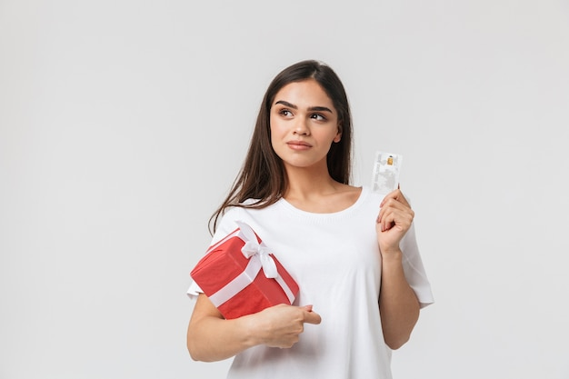 Retrato de uma bela jovem casual vestida de pé, isolada no branco, segurando uma caixa de presente, mostrando o cartão de crédito