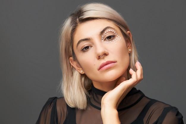 Retrato de uma bela jovem caucasiana com corte de cabelo elegante, piercing no nariz e cristais brancos ao redor de um olho, mantendo a mão no rosto. conceito de cuidados com a pele, maquiagem, cosméticos, cosmetologia e beleza