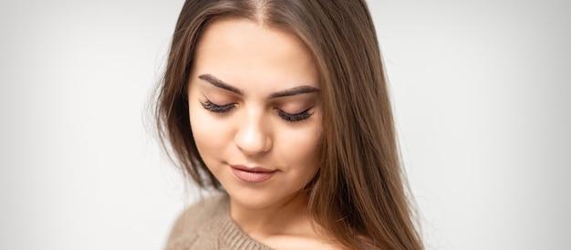 Retrato de uma bela jovem caucasiana com olhos fechados após procedimento de extensão de cílios e maquiagem definitiva