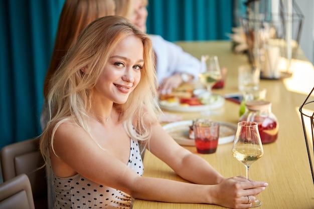 Retrato de uma bela jovem caucasiana com um copo de vinho branco luxuoso dentro de casa