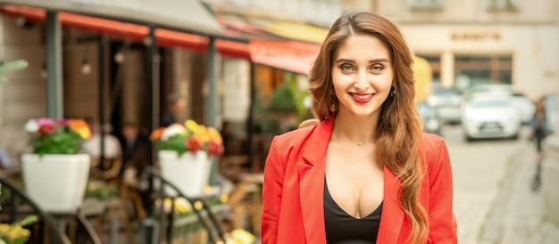 Retrato de uma bela jovem caucasiana sorrindo e em pé na rua da cidade olhando para a câmera ao ar livre
