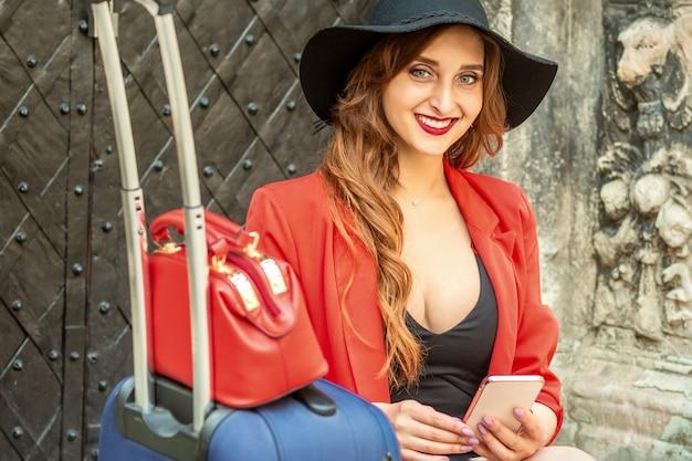Retrato de uma bela jovem caucasiana viajando, sentada à porta com uma mala e um smartphone, sorrindo e olhando para a câmera ao ar livre