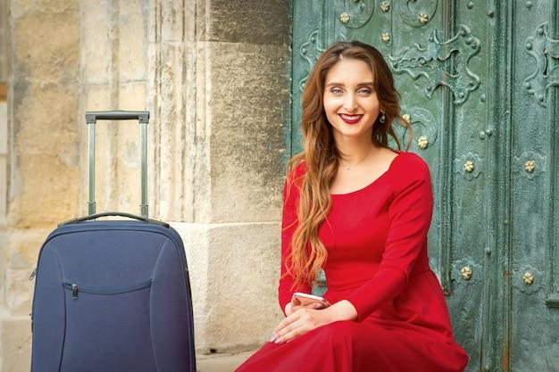 Retrato de uma bela jovem caucasiana viajando sentada na porta com uma mala, sorrindo e olhando para a câmera ao ar livre