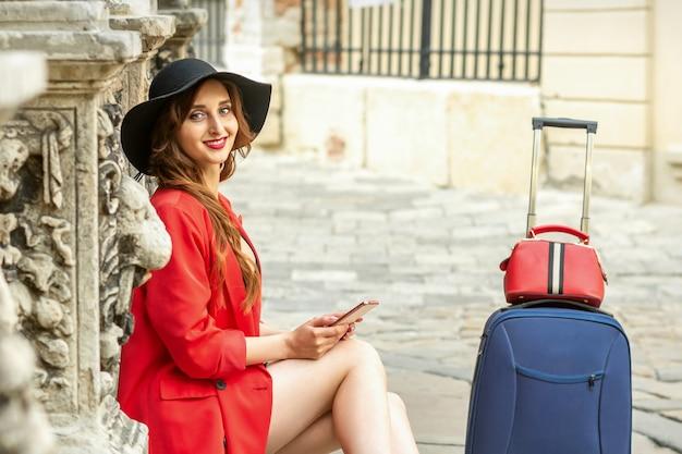 Retrato de uma bela jovem caucasiana viajando sentada na rua com uma mala, sorrindo e olhando para a câmera ao ar livre
