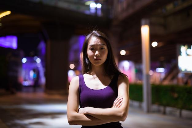 Retrato de uma bela jovem chinesa ao ar livre à noite